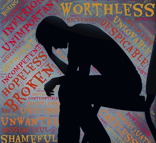 Cyberbullying: A photo of harsh and negative words surrounding a person and them dealing with it by going through mental health problems.