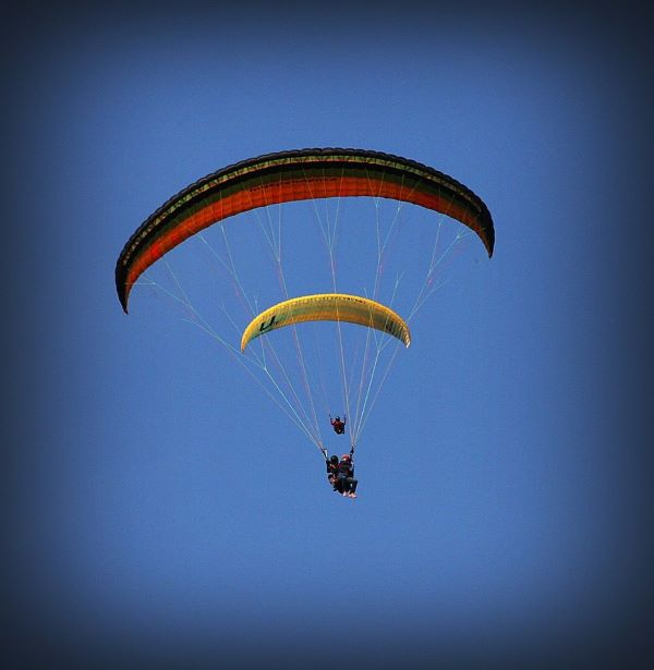 Tandem paragliding and a solo paraglider in the air