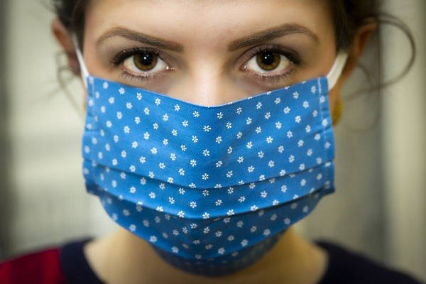 Close up of a woman wearing a fashionable mask in place of the drab and disposable surgical mask.
