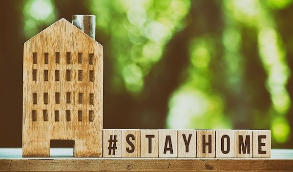 A hashtag of stay at home written out from wooden blocks and a wooden house next to it. This has caused many first year university students to miss out on many experiences.