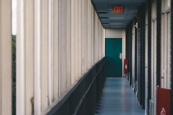 An empty hallway of a school residences with an exit sign at the end.