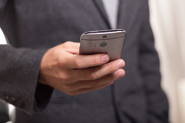 A hand taping on a smartphone and wearing grey suit.
