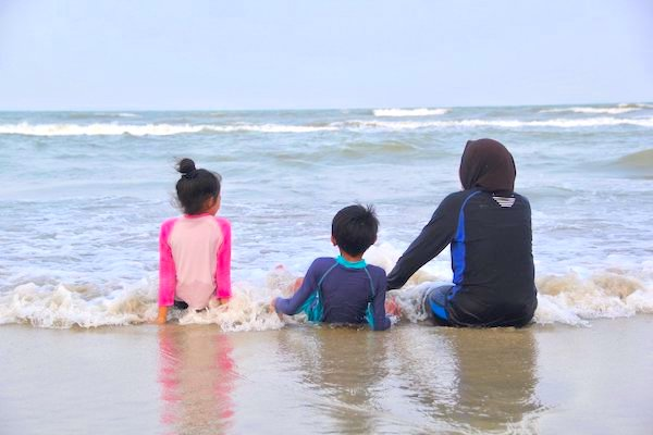 Three kids relaxing at the ocean looking out into the horizon.