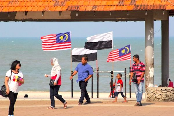 The Pahang and Malaysian flag standing in the background, and local citizens walking pass by.