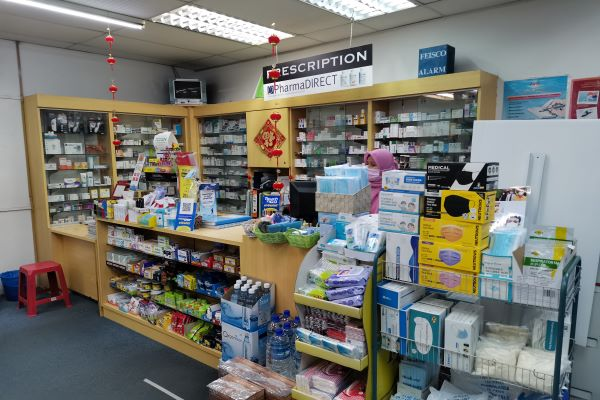 A pharmacist stands between shelves of medication and drugs.