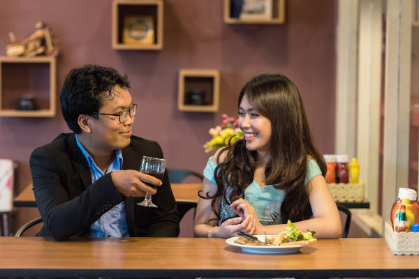 Two people sharing a meal and enjoying themselves on their first date.
