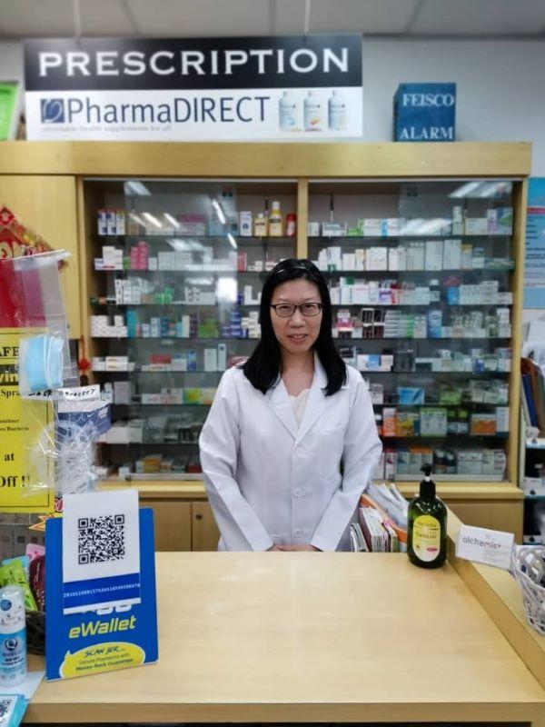 Meet our friendly neighbourhood pharmacist, Peh Mui Lee, behind the counter with prescription drugs behind her.