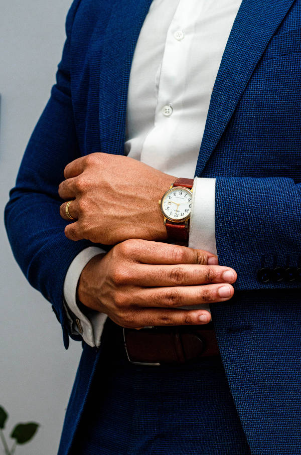 A gentleman dressed in a navy suit and white shirt, sporting a gold case, brown leather strap and white face with Roman numerals dress watch.
