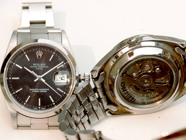 Two mechanical watches side by side, one showing the front (dial face) and one showing the exhibition case back, displaying the inner workings of the mechanical movement.