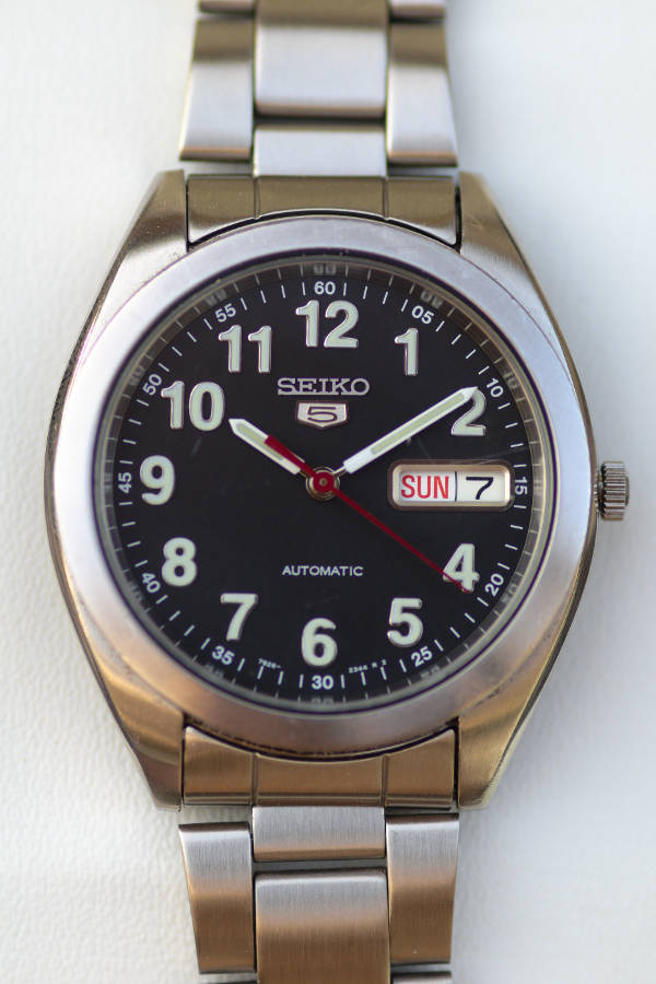 A close up of a Seiko 5, in brushed stainless steel case and bracelet, and a black dial with Roman numerals.