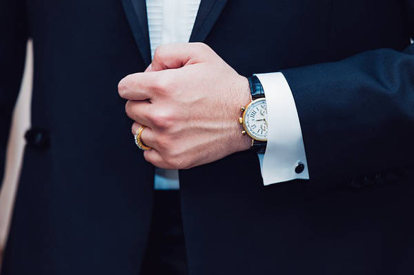 Close up of a gentleman's wrist, showcasing an elegant dress watch, partially hidden underneath the shirt cuff, which in turn peeks out from underneath of a dark jacket cuff.