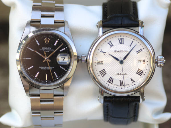Stainless steel Rolex Oyster Perpetual Date in black dial, and Sea-Gull M186S in white dial and black leather strap, wrapped around a watch cushion.