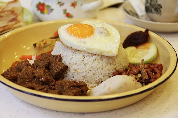 A plate of beef rendang with nasi lemak and a fried egg on top.