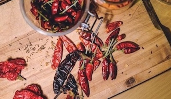 A chopping board of dried chillies with fennel seeds poured everywhere.