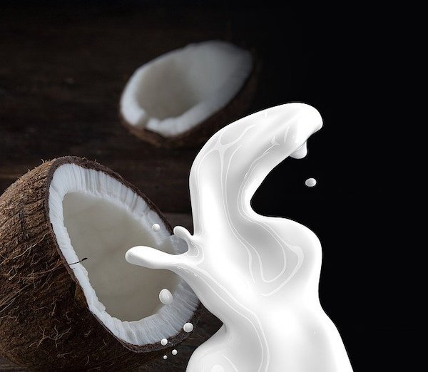 A coconunt sliced in half pouring out coconut milk, a common ingredient used by Malaysian mums.