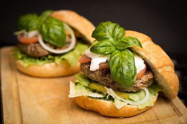 Two beef burgers full of lettuce, onion and tomato with a basil on top.