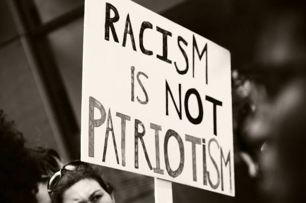 Woman protesting racism with a sign that says, 'Racism Is Not Patriotism.'