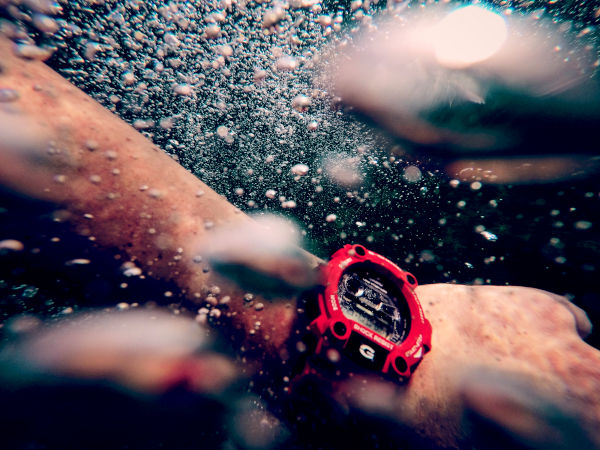 A close up of a Casio G-Shock on the wrist of a swimmer, as he paddles himself forward underwater.