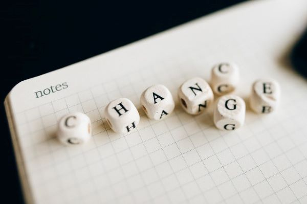 """White and black dice forming the word """"Change"""" on top of a notebook"""