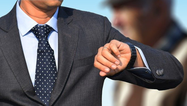 A man wearing business suit and tie, raising his wristwatch up to be read.