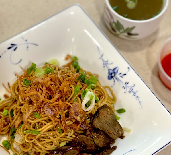 A kolo mee plated nicely topped with fried onions, spring onions, sliced beef with a side of chilli sauce and beef broth soup.