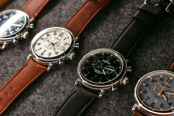 A series of wristwatches on a grey felt display tray, displaying the different designs.