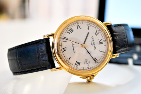 Raymond Weil Maestro dress watch, showcasing the typical characteristics of a dress watch. Round gold case, black hands and  Roman numerals for each hour marker against a clean which background of the dial. Complete with a black alligator leather strap.
