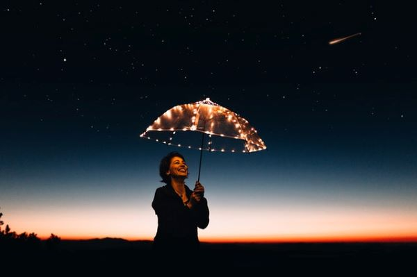 Woman holding an umbrella with light looking at a shooting star blazing across the night sky