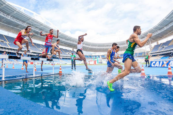 Wide angle view of athletes jumping over hurdles, as they land on a puddle of water on the track.