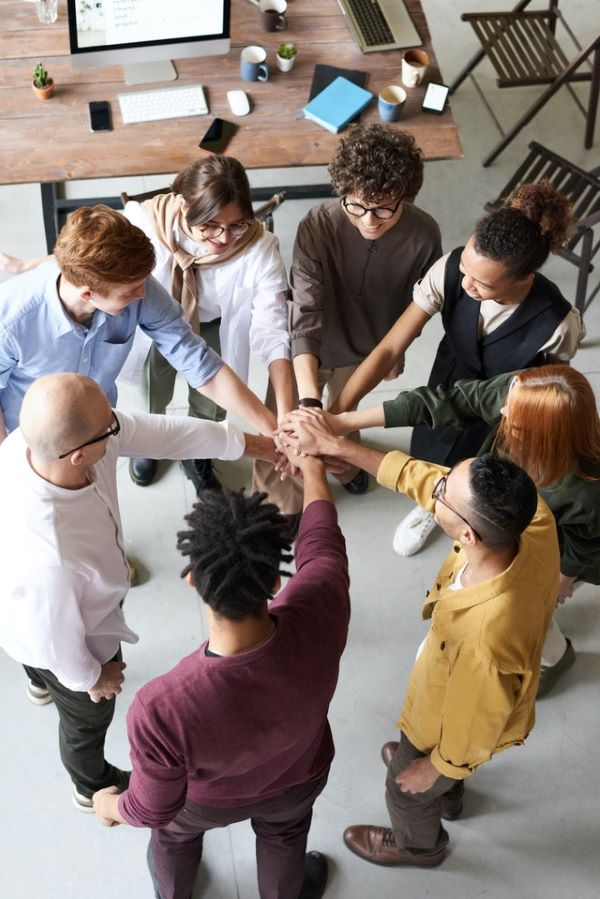 Brutal team of 8 employees holding each other's hands