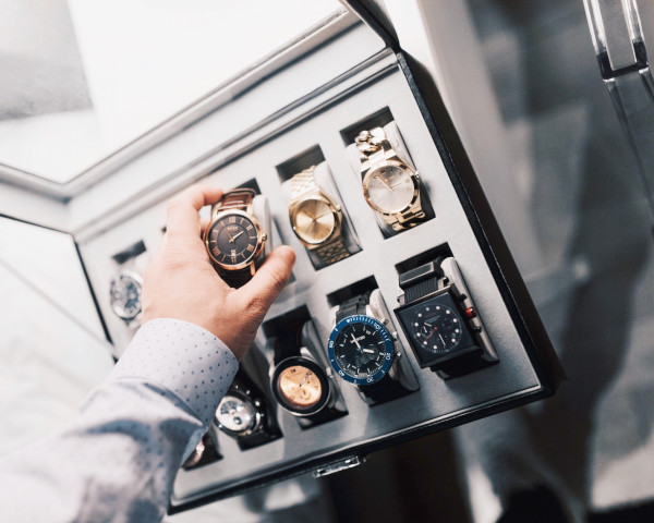A hand reaching out to retrieve one watch from a ten-watch display box. This represents an abundance of watches that one really needs.