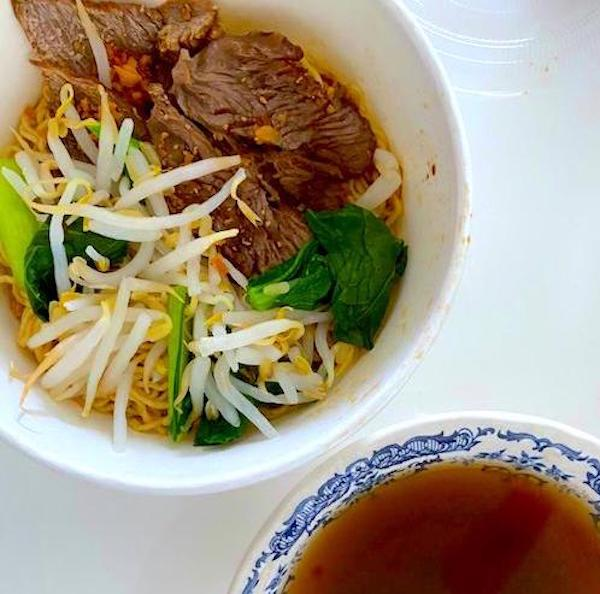 A kolo mee, noodle dish, bought from a shop with a bowl of soup next to it.
