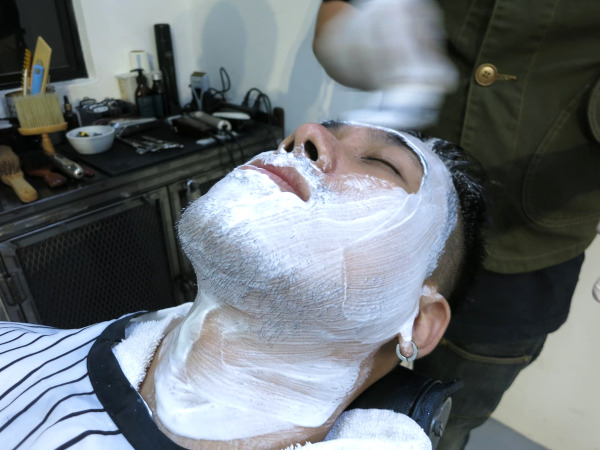 Barber lathering shaving soap on the face of the author