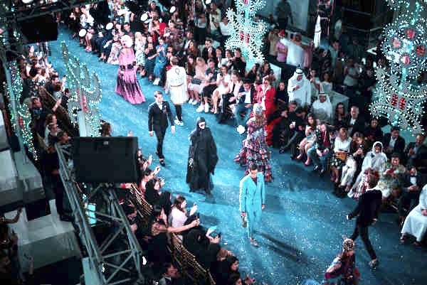 Models parading exaggerated costumes on the runway packed with fashion enthusiasts such as their clients and the press.