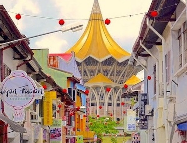 An alleyway somewhere in Kuching overlooking a yellow building.