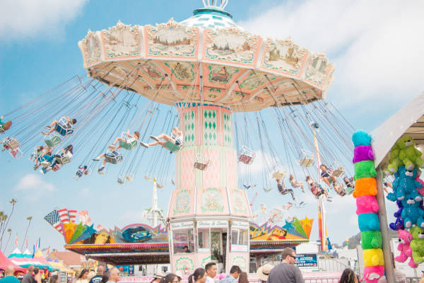 People riding on funfair swing ride at daytime