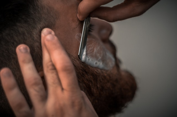 Close up of a man getting a professional shave by a barber.