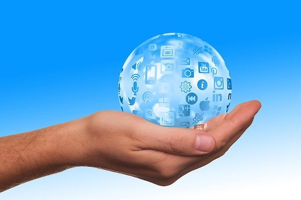 A man's hand holding a glass globe with social media icons surrounding it.
