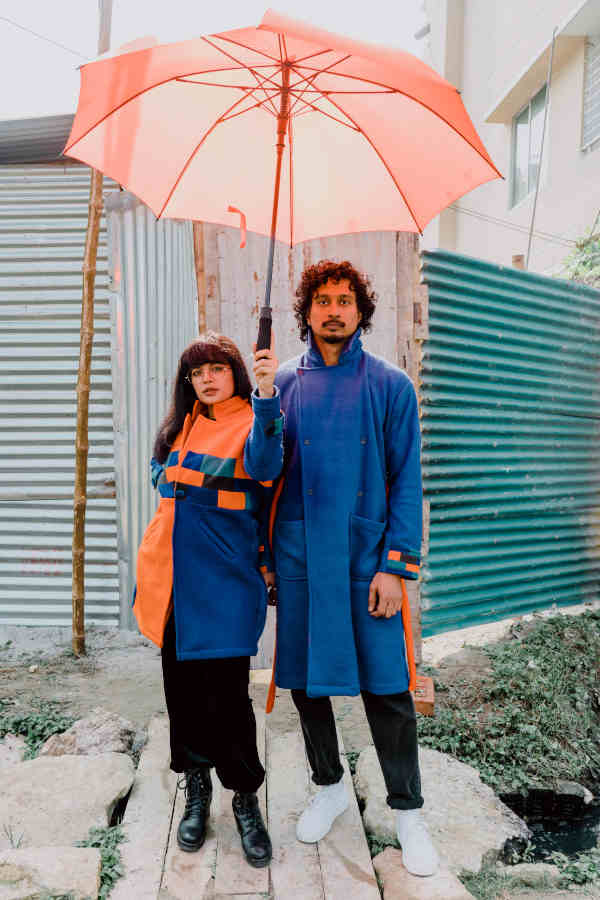 A pair of male and female models wearing Broqué's orange and blue patchwork lounge coats. Male model is holding a matching orange umbrella.