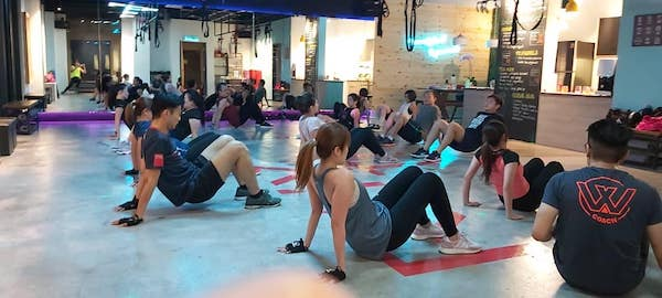 A gym full of people exercising together with Tabata.