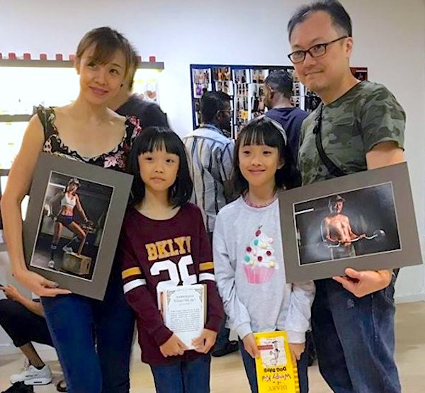 Dallas, Melina and their two children posing while showing their Body Transformation Challenge photos with the help of Tabata.