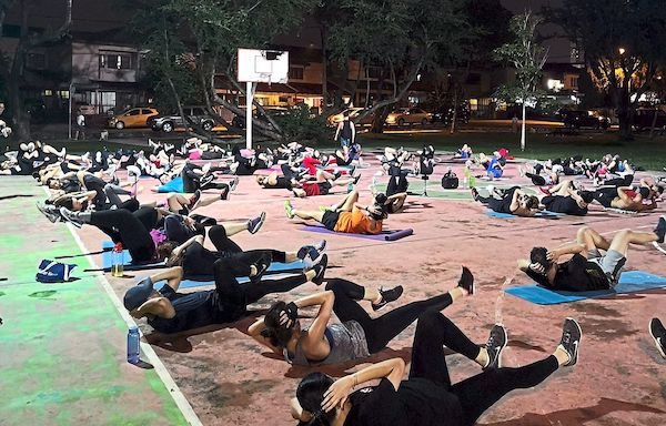 Many people working out to Tabata together outside at the basketball court.