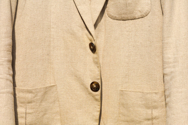 """Close-up of an unbleached linen sport jacket, showcasing the dark coloured contrasting buttons. Also displaying the three front patch pockets, popularly known as """"three patches""""."""