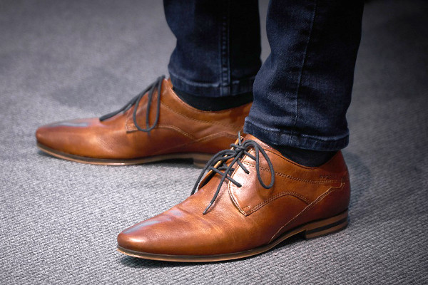 A pair of medium brown Derby shoes, showcasing the open lacing system, as opposed to Oxford's closed lacing system.