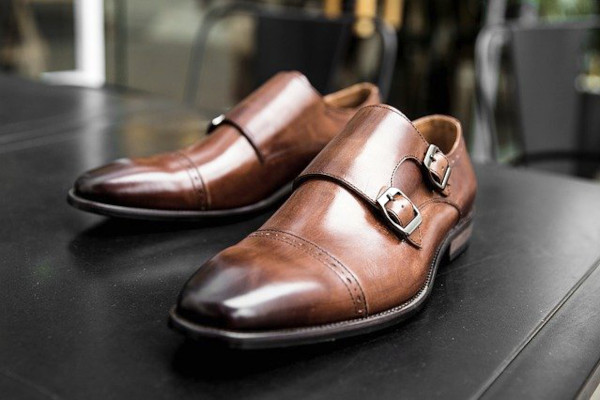 """A pair of medium brown double monk straps, with cap toe and minimal brogueing. The toe comes with """"burnt out"""" design, with the tip of the toe graduating from dark brown to the medium brown of the rest of the shoe."""