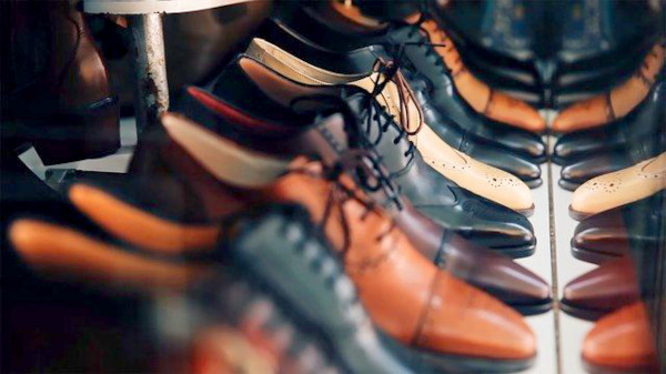 Window display of a shoe shop, showcasing various types of dress shoes.