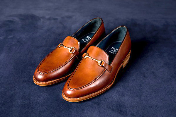 A pair of medium brown horse-bit loafers, showcasing the bronze coloured hardware across the vamp/tongue.