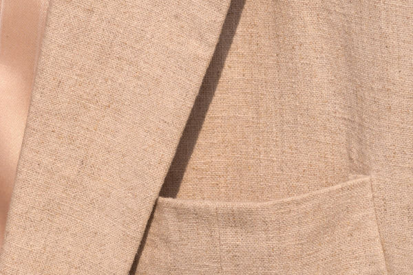 Close-up on the chest piece of a linen sport jacket, showcasing the texture of the fabric, and the loose weave which contributes to its breathability.