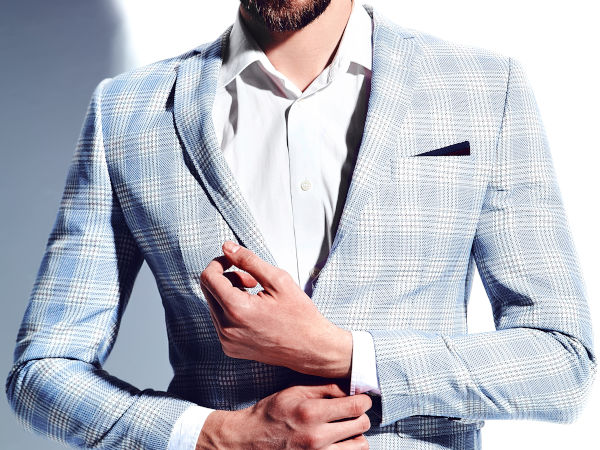Close up of a torso and arms of a man, displaying a blue and white Glen check sport jacket, over a white shirt. The image is completed with a contrasting dark pocket square as a visual interest.