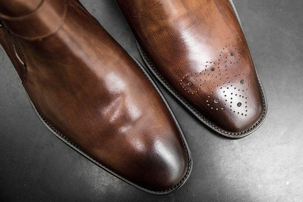 Toes of two types of dress shoes, one with a plain toe, and the other with decorated with a medallion.